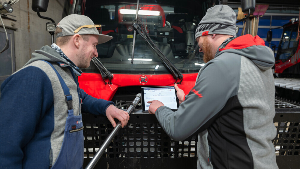Zwei Personen bedienen SNOWsat Maintain in der Werkstatt.